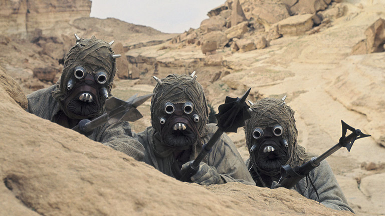 Tusken Raiders from Star Wars, wearing tan robes and yielding weapons.