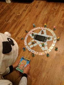 A person dressed in Animal Crossing attire, holding a copy of Animal Crossing sitting folk, praying over a pentagram made of Animal Crossing amiibo cards with a Nintendo Switch in the middle.
