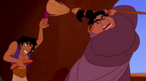 Aladdin hides from the heavy-set woman in charge of the harem who is swinging a broom at him.