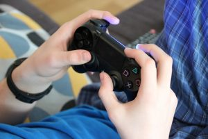 Close up of hands holding a video game controller.