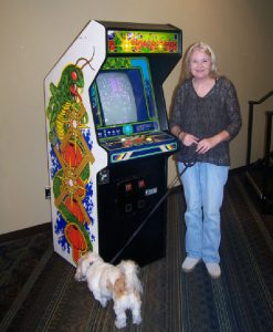 "A woman in front of the ""Centipede"" arcade machine, with a dog on a leash."