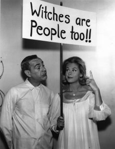 The witch Samantha from Bewitched holds a sign that reads Witches Are People Too