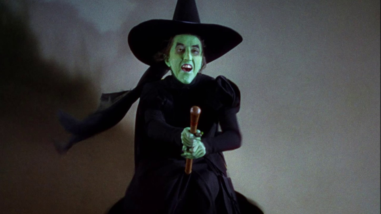 A green witch rides a broomstick