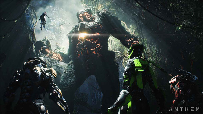 "Screenshot of ""Anthem,"" depicting what looks like a party of four armored warriors, with a giant monster towering over them in a dark jungle."