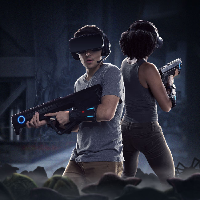 "Promotional image of ""Alien: Descent."" It shows two people wearing VR gear (visor headset, plastic gun, lightweight devices on their arms and legs) while in a dark shadowy area, surrounded by what seems to be alien eggs and at least one facehugger alien."