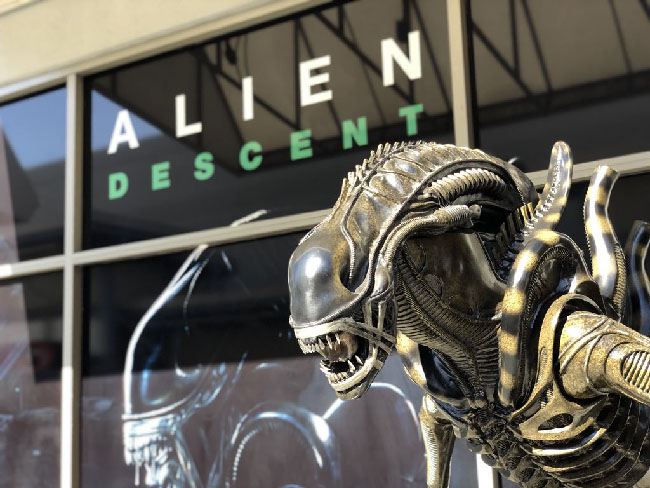 "Photo of the exterior of the ""Alien: Descent"" building and Xenomorph alien statue. The building has a poster of ""Alien: Descent"" with an image of the Xenomoprh alien on it."