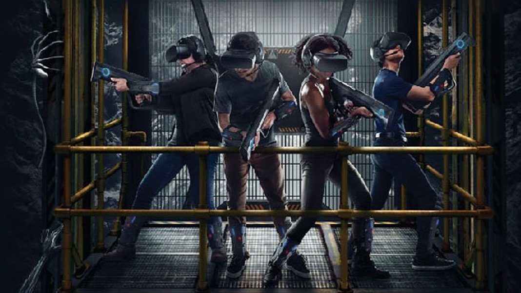 "Promotional image of ""Alien: Descent."" It shows four people wearing VR gear (visor headset, plastic gun, lightweight devices on their arms and legs) on a yellow metal lift, with facehugger aliens crawling around."