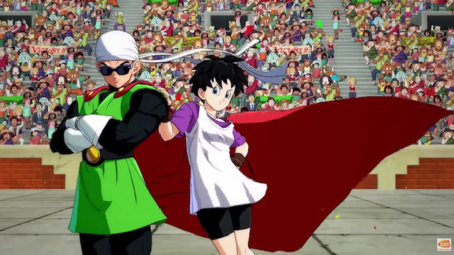 "Image of Videl and the Great Saiyaman (a.k.a. Gohan) from ""Dragon Ball FighterZ."" Videl is leaning against the Great Saiyaman. Videl is a young woman with short dark hair, wearing a white tank top over a purple shirt, black shorts, and fingerless gloves. The Great Saiyaman is a young man that looks like a superhero, with clothing like a red cape, green tunic, and dark sunglasses."