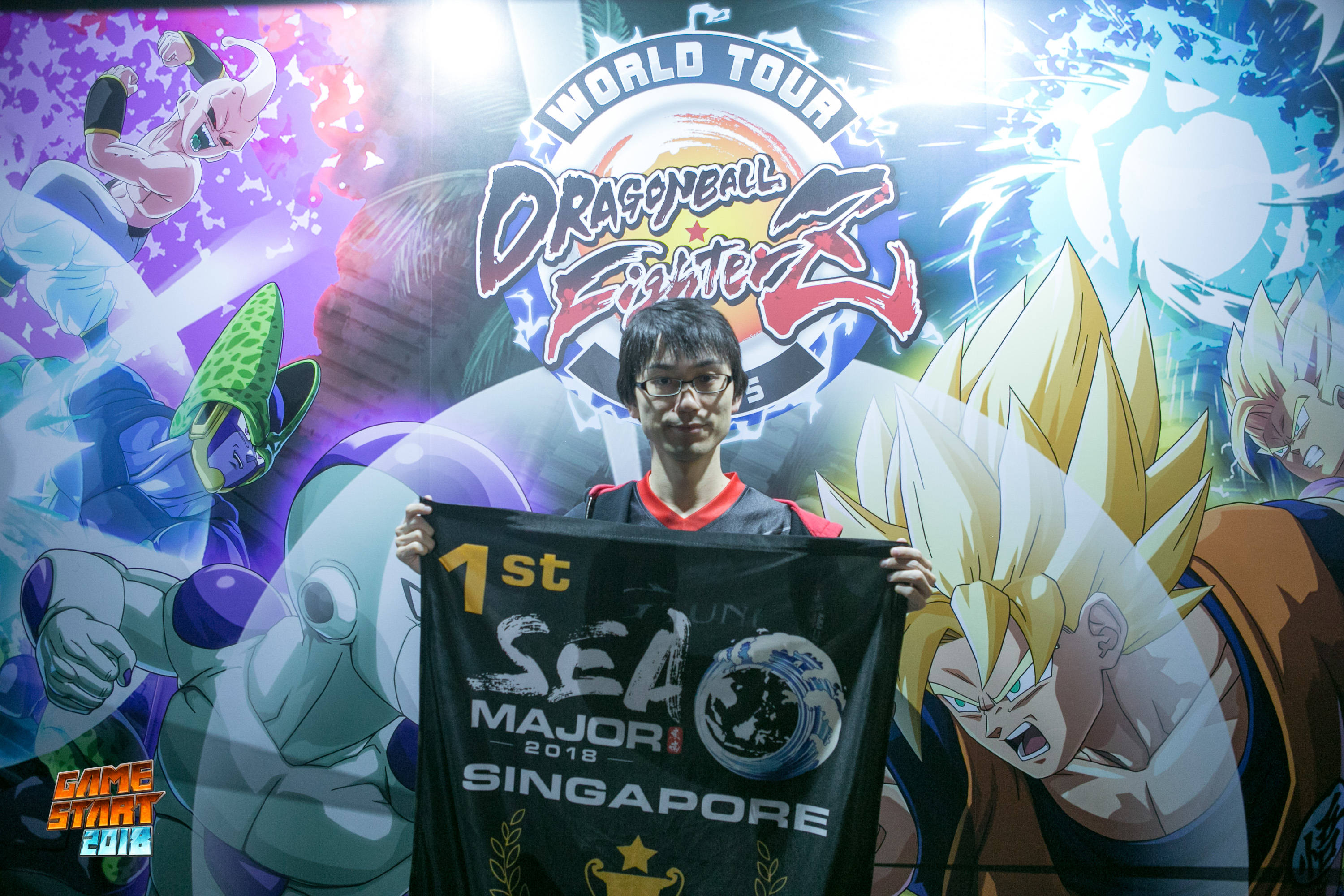 "Photo of Ryota ""Kazunoko"" Inoue holding a first place South East Asia Major 2018 banner, and standing in front of a ""Dragon Ball FighterZ"" World Tour poster."